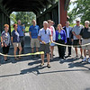 JOHN KLINE | THE GOSHEN NEWS <br /> Dick Cook, president of the Friends of the Middlebury Parks, center, is joined by other community trail supporters and stakeholders for the official ribbon-cutting of the town's newest trail, the Rock Run Trail, at the Essenhaus covered bridge in Middlebury Saturday afternoon.