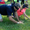 JOHN KLINE | THE GOSHEN NEWS <br /> Middlebury resident Jason Wogoman, left, and daughter Tenille, 9, smile as they search for pennies in the grass while blindfolded during the Edward Jones pennies challenge, part of the first-annual TrailsFest TrackDown scavenger hunt Saturday in Middlebury.