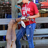 Roger Schneider | The Goshen News<br /> This Nubian goat nibbles at its leash as Madison Burton, 18, of Topeka, checks her phone. Burton said she is a member of the Dog Club but also shows goats at the fair.