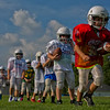 JAY YOUNG | THE GOSHEN NEWS<br /> Nine-year-old Kaiden Leach, of Goshen, takes off with the football as he runs through a running back drill while competing in the Goshen Junior Football League free summer camp Wednesday evening at Pringle Park.
