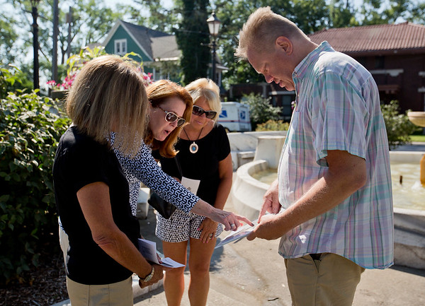 JAY YOUNG | THE GOSHEN NEWS<br /> From left, Bobbi Meyers, Janet Evanega and Peggy Forrest Presser look at a historic photo shown by tour guide Steve Gruber during his Kings of the Hill tour in Elkhart Wednesday morning. The 45 minute long walking tour covered approximately half a mile and made 11 stops. Gruber spent the tour talking about the well-known families of Elkhart around the turn of the 20th century.