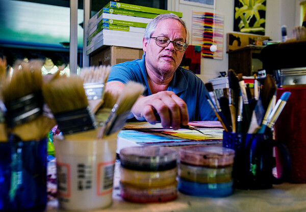 JAY YOUNG | THE GOSHEN NEWS<br /> Tucked behind numerous brushes and paints, New Paris based artist Kenton Yoder works at his in-home studio Friday afternoon. Yoder, who has been painting for about four years, said he got the itch to start painting after watching his daughter do a watercolor project.