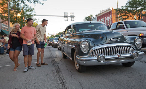 JAY YOUNG   THE GOSHEN NEWS<br /> A group of spectators step out into Main Street to get a closer look at a car during the July First Fridays Cruisin' Reunion Friday evening in downtown Goshen.