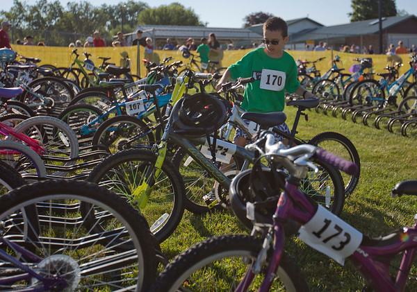 JAY YOUNG | THE GOSHEN NEWS<br /> David Stutzman, of Goshen, pulls his bicycle off the bike rack as he transitions from swimming to cycling during 13th annual Kids' & Teens' Try-Athlon hosted by the Goshen Parks and Recreation Department at Shanklin Park Saturday morning.