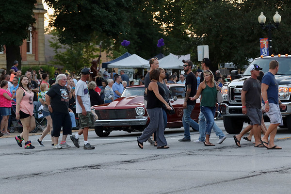 JAY YOUNG   THE GOSHEN NEWS<br /> Pedestrians glance over at old cars that are stopped at a red light as they cross Main Street during the July First Fridays Cruisin' Reunion in downtown Goshen Friday evening.