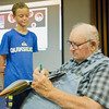 "JAY YOUNG | THE GOSHEN NEWS<br /> Curran Hartzler, 11, of Hendersonville, North Carolina, watches as John Nunemaker autographs a copy of the book ""Seagoing Cowboys"" Monday afternoon at the Goshen Public Library. After World War II, Nunemaker and about 7,000 other seagoing cowboys sailed across the Atlantic Ocean to bring livestock to areas devastated by the war."