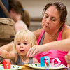 JAY YOUNG | THE GOSHEN NEWS<br /> Three-year-old Paizley Wyse gets some help from her mother, Heather, both of Middlebury, as they create a marble maze Monday afternoon at the Middlebury Community Public Library. Participants glued strips of colored construction paper to paper plates, forming loops and paths that they would then guide a marble through.