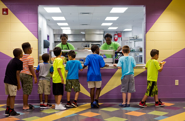 JAY YOUNG   THE GOSHEN NEWS<br /> A group of boys wait in line as Alicia Malone, left, and Dajah Frye serve lunch at the Goshen Boys & Girls Club Monday afternoon. The club opened Monday after a massive renovation project that added 20,000 square feet to the building. It was closed since June 2016.