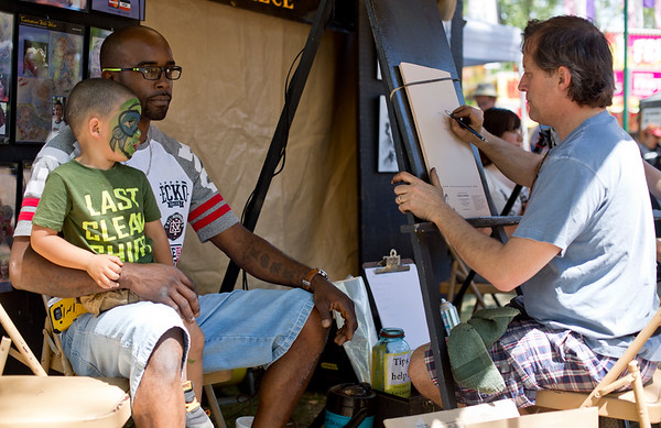 JAY YOUNG   THE GOSHEN NEWS<br /> Three-year-old Baiylin Williams sits on his dad's Demiris, both of Elkhart, lap as they pose for a caricature drawing by Warsaw artist Don Swartzentruber during the Rhapsody in Green Music Festival at Island and Bicentennial Parks in Elkhart.