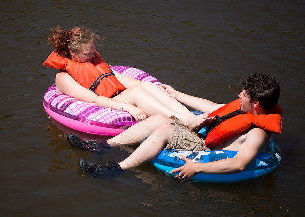 JAY YOUNG | THE GOSHEN NEWS<br /> Francesca Carlen and Chris Flora, both of Elkhart, lock their tubes together as they float down the Elkhart River during the Rhapsody in Green Music Festival at Island and Bicentennial Parks in Elkhart.