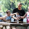 JAY YOUNG | THE GOSHEN NEWS<br /> From left, Haley Garrett, 13, Chase Garrett, 8, Alex Smith, 15, and Angel Smith, 13, crowd around a water fountain to fill up their water bottles during the Rhapsody in Green Music Festival at Island and Bicentennial Parks in Elkhart.