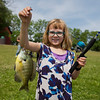 JAY YOUNG | THE GOSHEN NEWS<br /> Six-year-old Sierra Adkins, of Goshen, proudly shows off one of the bluegills she caught during a fishing derby hosted by the Goshen Parks and Recreation Department Saturday morning at Fiddler Pond.