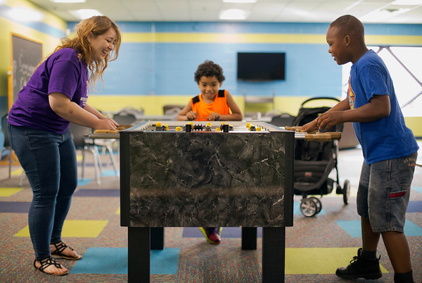 JAY YOUNG | THE GOSHEN NEWS<br /> Seven-year-old Elijah Rivas, center, watches with excitement as his mom, Boys and Girls Club employee Dominique Rivas, plays a game of foosball against Richard Childress, 9, during an open house at the club Saturday morning.