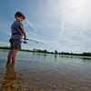 JAY YOUNG | THE GOSHEN NEWS<br /> Six-year-old Jonathan Noffsinger, of Granger, looks over his shoulder as he stands ankle deep in water waiting for a bite during a fishing derby hosted by the Goshen Parks and Recreation Department Saturday morning at Fiddler Pond.