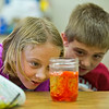JAY YOUNG | THE GOSHEN NEWS<br /> Seven-year-olds Jaiden Vardaman, left, and Lucas Miller watch as colored water and oil mix, making a make-shift lava lamp during the Bright Time summer camp at Bethany Christian Tuesday afternoon.