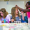 JAY YOUNG | THE GOSHEN NEWS<br /> Nine-year-old Daphcar Lehman, right, is unable to hold back her laughter as she places a handful of mini-marshmallows on top of Pippin Stutsman's, 8, head while Isabella Yoder, 10, all of Goshen, quietly works on her project during the BrightTime Summer Camp at Bethany Christian Tuesday afternoon.