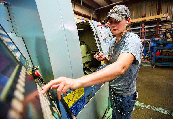 JAY YOUNG | THE GOSHEN NEWS<br /> Cutting Edge Machine and Tool, Inc. employee Kellie Anglemyer, of Goshen, punches commands into the CNC machine she operates as she makes pins for wheelchair lifts Thursday morning. Anglemyer, who has been with the company for six years, started while still in high school as an assembler.