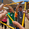 JAY YOUNG | THE GOSHEN NEWS<br /> Goshen High senior Brandon Holley helps hold up playground equipment so Austin Francis, of Kalamazoo, Michigan, can tighten a bolt as they help assemble new playground equipment Thursday afternoon at Parkside Elementary School.