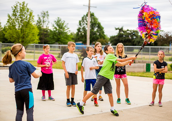 JAY YOUNG | THE GOSHEN NEWS<br /> Candy flies as 8-year-old Gideon Miller, of Goshen,  lands a solid hit on a giant rainbow piñata made from a balloon and paper mache Friday morning during the BrightTime Camp at Bethany Christian.
