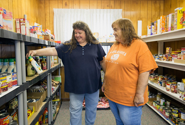 JAY YOUNG | THE GOSHEN NEWS<br /> Fairfield food pantry volunteer Carol Smith shows off a bottle of ranch dressing to director Sandi Sizemore Tuesday afternoon. Smith said that it was rare for the pantry to have ranch dressing in stock and she expected it to go fast.