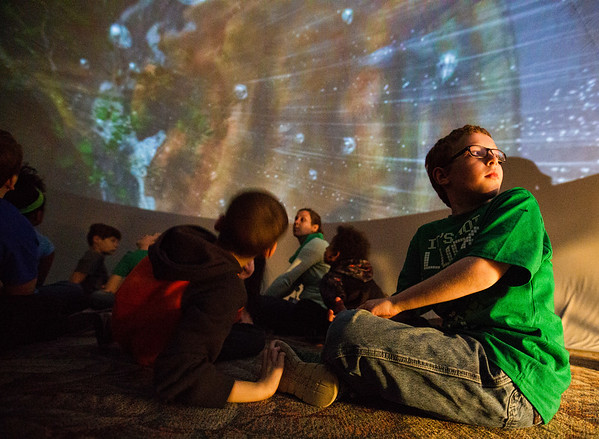 JAY YOUNG | THE GOSHEN NEWS<br /> Woodland Elementary second-grader Dyllan Bowers looks back over his shoulder to see the whole picture as he and his classmates sit inside a portable star lab to watch a movie projected onto the ceiling about the history of the Earth at ETHOS Science Center during a class fieldtrip Friday Morning.