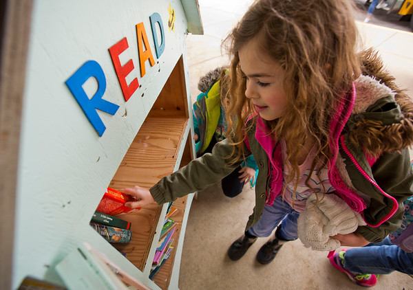 JAY YOUNG | THE GOSHEN NEWS<br /> York Elementary first-grader Allie Graber places books inside a free lending library stand outside of the elementary school  Monday afternoon.