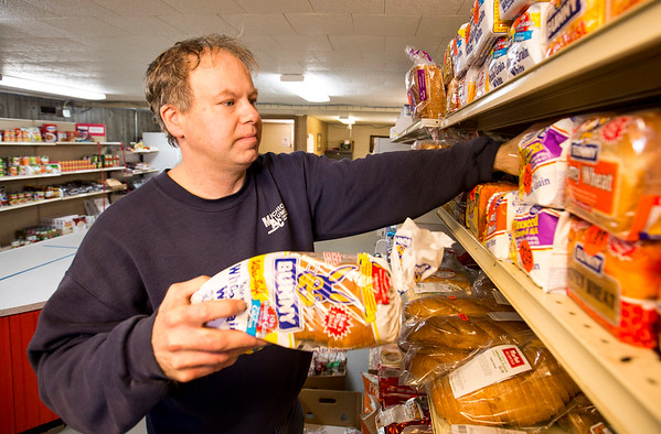 JAY YOUNG | THE GOSHEN NEWS<br /> Chad Brich, a 14-year volunteer at the Family Christian Development Center, stocks the food pantry shelves with bread Tuesday, March 21, 2017.
