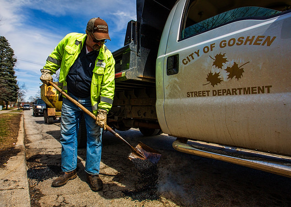 JAY YOUNG | THE GOSHEN NEWS<br /> Todd Turner, with the Goshen Street Department, uses hot asphalt to fill in a pothole on Eighth Street need the intersection of U.S. 33 Tuesday afternoon. Turner said he had filled over a hundred potholes so far today.