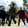 JAY YOUNG | THE GOSHEN NEWS<br /> West Noble Elementary kindergarteners Bentley Mahon, left, and Christian Castro run down the track during recess Wednesday afternoon in Ligonier. Students at the school walk laps every day as part of a fitness program. To date, they have walked 26,289 miles total.