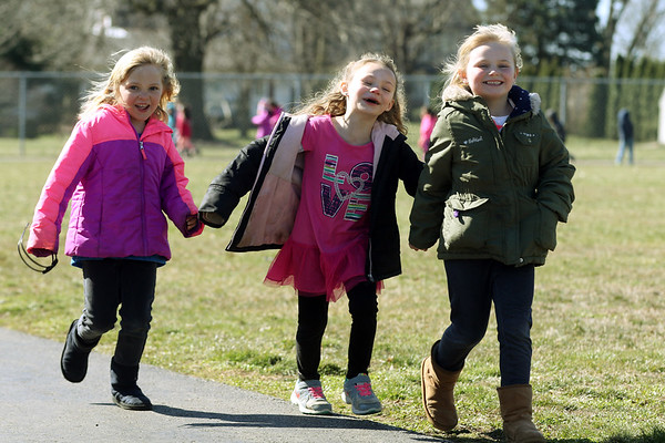 JAY YOUNG | THE GOSHEN NEWS<br /> West Noble Elementary kindergarteners, from left, Clarinda Button, Makenzie Crawford and Ella Lundy hold hands as they walk laps around the track during recess Wednesday afternoon in Ligonier. Students at the school walk laps every day as part of a fitness program. To date, they have walked 26,289 miles total.
