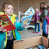 JAY YOUNG | THE GOSHEN NEWS<br /> York Elementary first-grader Leea Fodge grabs a handful of books while classmates Allie Graber, right, and Alyson Snyder help to place books inside the free lending library outside the elementary school Monday afternoon.