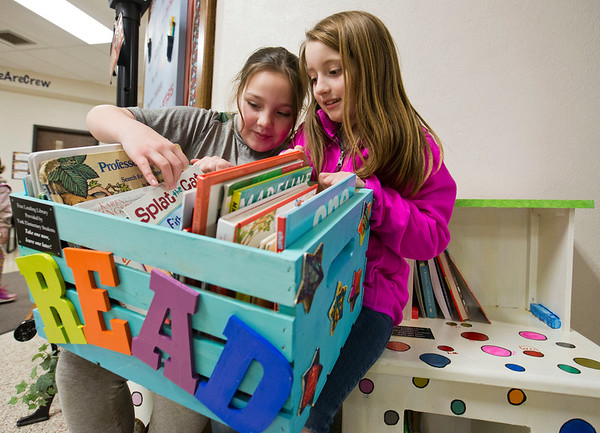 JAY YOUNG | THE GOSHEN NEWS<br /> York Elementary third-grade students Becky Chupp, left, and Leslie Miller browse through a crate of books Monday afternoon at the school. Students at the school worked on a service project in which they created free lending libraries.