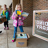 JAY YOUNG | THE GOSHEN NEWS<br /> York Elementary first-grader Alyson Snyder stops to browse a book while classmates Allie Graber, left, and Leea Fodge carry a box of books to be placed inside the free lending library outside the elementary school Monday afternoon.