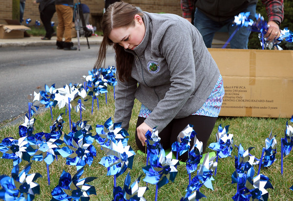 SHERRY VAN ARSDALL | THE GOSHEN NEWS<br /> Shannon Wright helped plant 3,000 pinwheels around the lawn in front of the Child and Parent Services building in Elkhart Friday afternoon. Wright works with the Elkhart County Prosecutor's Office in the child support division.