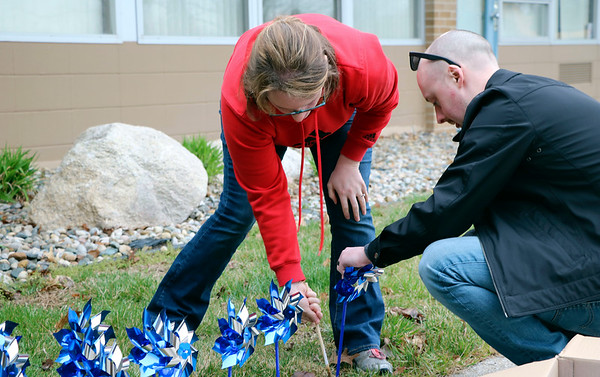 SHERRY VAN ARSDALL | THE GOSHEN NEWS<br /> At left, Kim Lloyd and her husband, Craig Lloyd, helped plant 3,000 pinwheels around the lawn in front of the Child and Parent Services building in Elkhart Friday afternoon.