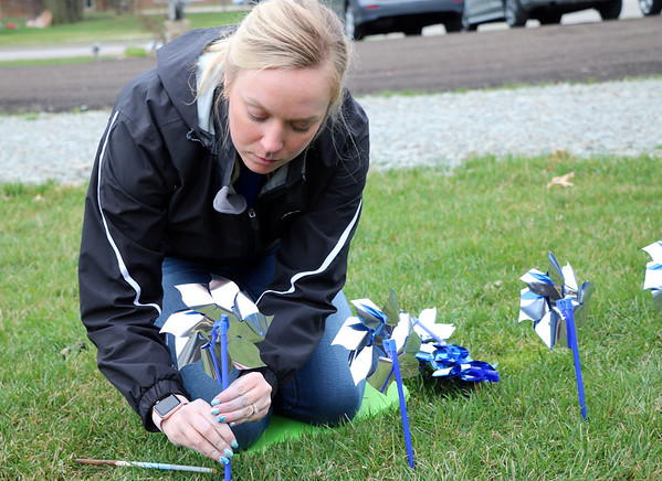 SHERRY VAN ARSDALL | THE GOSHEN NEWS<br /> Olga Glossett helped plant 3,000 pinwheels around the lawn in front of the Child and Parent Services building in Elkhart Friday afternoon. Glossett works with the Elkhart County Prosecutor's Office.
