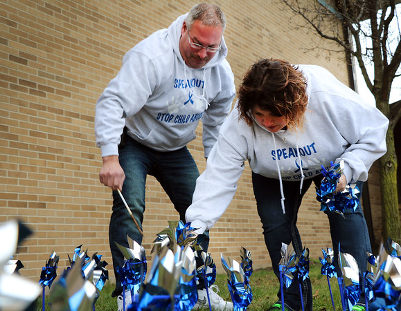 SHERRY VAN ARSDALL | THE GOSHEN NEWS<br /> At left, Tony Garza and his wife, Angie Garza helped plant 3,000 pinwheels around the lawn in front of the Child and Parent Services building in Elkhart Friday afternoon.<br /> Garza's grandson, Kirk Coleman, died October 2014 while in the care of former babysitter, Jackie Rolston.