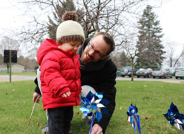 SHERRY VAN ARSDALL | THE GOSHEN NEWS<br /> At right, Justin Allen and his 19-month-old son, Drake Allen, helped plant 3,000 pinwheels around the lawn in front of the Child and Parent Services building in Elkhart Friday afternoon.<br /> Allen is the Elkhart County CASA director.