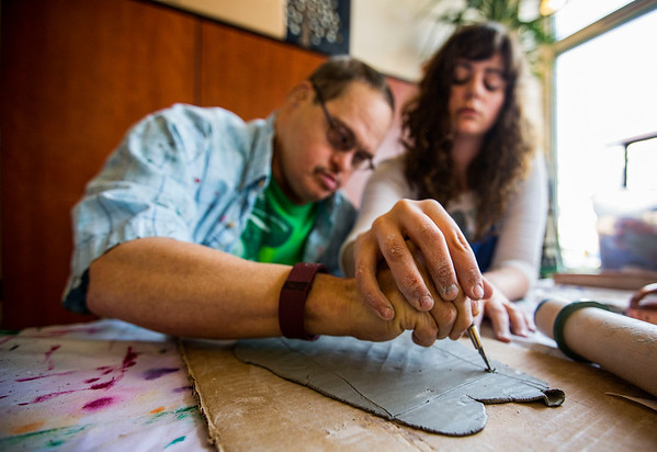 JAY YOUNG | THE GOSHEN NEWS<br /> With clay covered fingers, Michelle Jones carefully guides Ritchie Mann's hands as they cut away excess clay from a ceramic mug they were making Wednesday morning at Gaining Grounds in Goshen.