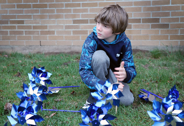SHERRY VAN ARSDALL   THE GOSHEN NEWS<br /> Devyn Clements of Elkhart helped plant 3,000 pinwheels around the lawn in front of the Child and Parent Services building in Elkhart Friday afternoon.