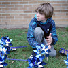 SHERRY VAN ARSDALL | THE GOSHEN NEWS<br /> Devyn Clements of Elkhart helped plant 3,000 pinwheels around the lawn in front of the Child and Parent Services building in Elkhart Friday afternoon.