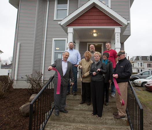JAY YOUNG | THE GOSHEN NEWS<br /> From left, Larry Gautsche, LaCasa president; Brad Hunsberger,  vice president of real estate development; Bard Hassan, LaCasa board chair; Mark Morris, carpenter for LaCasa; Grace Bonewitz, volunteer with Elkhart County Community Foundation; Julia Gautsche, Goshen city council; Aaron Lehman, real estate development manager; and David Daugherty, president of Goshen Chamber of Commerce attend a ribbon cutting ceremony on the front steps of 408 East Lincoln Ave. in Goshen Thursday afternoon. LaCasa recently finished renovating the property. It contains five units and the first tenants are expected the second week of April.