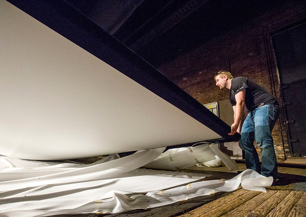 JAY YOUNG | THE GOSHEN NEWS<br /> Jake Drown, of Custom Sound Designs, lifts the bottom of a movie theater screen that he was installing inside of the Goshen Theater on Tuesday afternoon in preparation for the upcoming River Bend Film Festival.