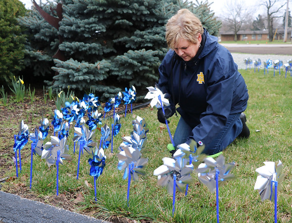 SHERRY VAN ARSDALL | THE GOSHEN NEWS<br /> Pam Benedix helped plant 3,000 pinwheels around the lawn in front of the Child and Parent Services building in Elkhart Friday afternoon. Benedix works with the Elkhart County Prosecutor's Office in the child support division.