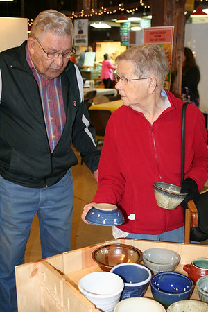 SHEILA SELMAN | THE GOSHEN NEWS<br /> Hilary, left, and Gladys Bertsche, Goshen, decide which bowls they want to take home Saturday at the Empty Bowl Project at the Goshen Farmer's Market.