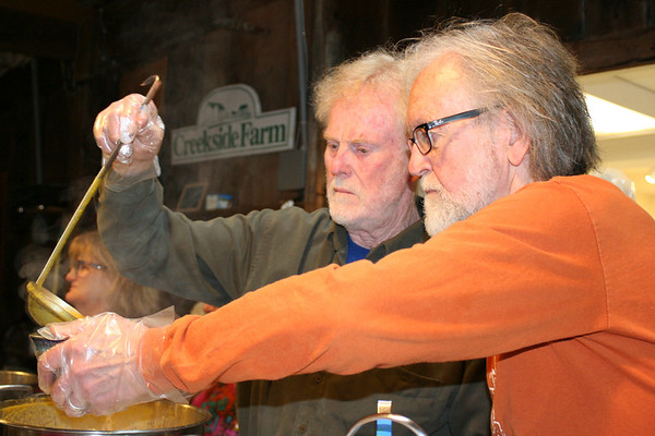 SHEILA SELMAN | THE GOSHEN NEWS<br /> A little bit of teamwork gets the job done as Dave Pottinger, left, and Jerry Lapp pour a bowl of soup for a customer Saturday during the Empty Bowl Project fundraiser at the Goshen Farmers Market.
