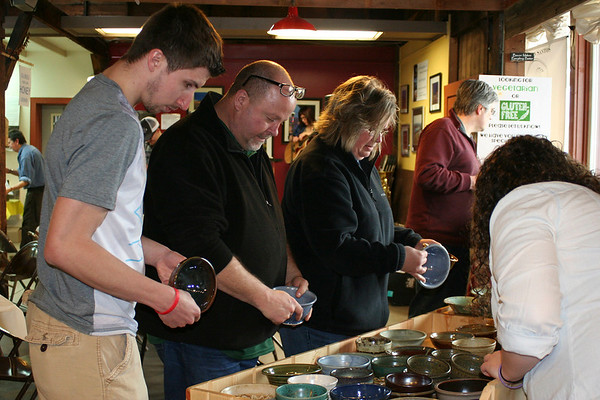 SHEILA SELMAN | THE GOSHEN NEWS<br /> Picking out pottery bowls for their soup are, from left, Jake Hutsell of Huntertown, Craig Rodman and Dawn Rodman, both of Goshen.