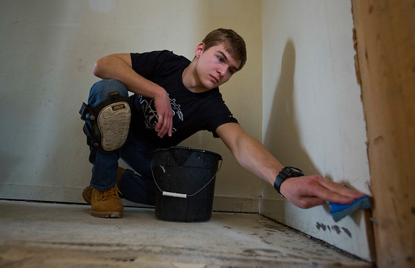 JAY YOUNG | THE GOSHEN NEWS<br /> Grand Valley State sophomore Conrad Frank uses a sponge to clean baseboards in a multi-family property  at 408 E. Lincoln Ave. in Goshen Monday morning. Frank is with a group of students from Grand Valley State University and Lewis University who are donating their spring break to volunteer with LaCasa to help restore the home. The house is part of LaCasa's East Lincoln Corridor Revitalization project. It is the first of five dilapidated multi-family dwellings that LaCasa is working to restore as part of the project.