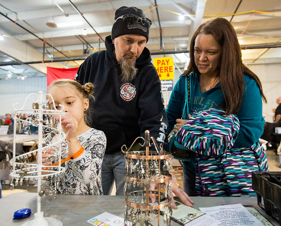 JAY YOUNG   THE GOSHEN NEWS<br /> Six-year-old Shay Shannon looks through earrings with her parents Scott and Maria, all of La Paz, at the Abate of Indiana's 32nd annual Region One Elkhart County Swap Meet on Sunday morning at the Northern Indiana Event Center in Elkhart.
