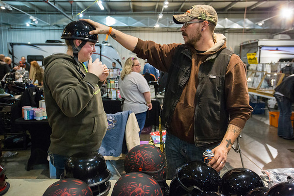 JAY YOUNG | THE GOSHEN NEWS<br /> Ryan Masten helps Tanya Welch, both of Centreville, Michigan, try on riding helmets at the Abate of Indiana's 32nd annual Region One Elkhart County Swap Meet on Sunday morning at the Northern Indiana Event Center in Elkhart.